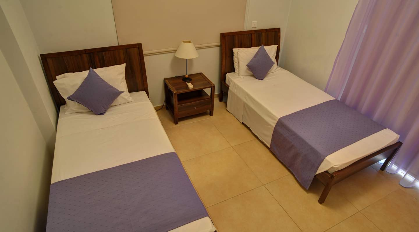 Purple coloured twin beds of three bedroom apartment at Paphos Aphrodite Sands Resort