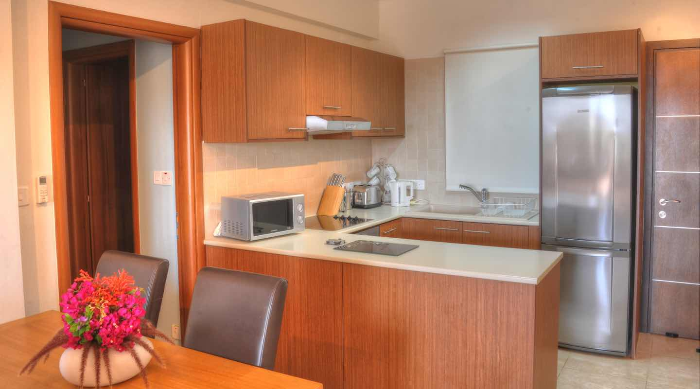 Kitchen and dining table of two bedroom apartment at Paphos Aphrodite Sands Resort