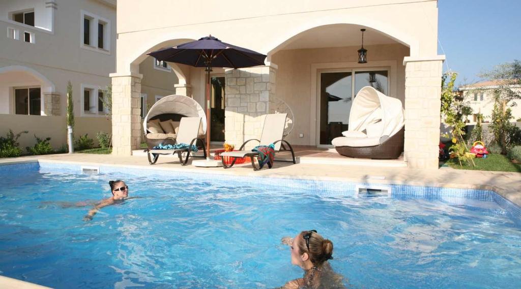 Elegant Girls Swimming In The Wimming Pool Of Villa At Paphos Aphrodite Sands Resort